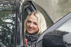 Young attractive woman with a cup of hot drink sits in the black car. Soft focus background Royalty Free Stock Images