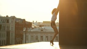A young attractive woman with curly hair performing dancing elements leaning on the tower - background of buildings - stock video