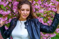 Young attractive woman with curly hair in white dress and black leather jacket smiles in blossom of pink sakura flowers
