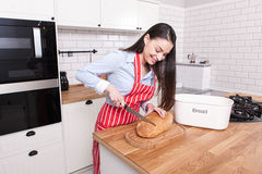 Young attractive woman cutting bread in kitchen. Stock Images