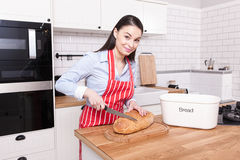 Young attractive woman cutting bread in kitchen. Stock Photography