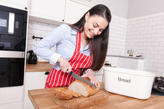 Young attractive woman cutting bread in kitchen. Royalty Free Stock Photos