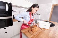 Young attractive woman cutting bread in kitchen. Royalty Free Stock Images