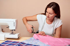 Young attractive woman cutting fabric Royalty Free Stock Image