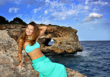 Young attractive woman on cyan glamour dress leaning on rock cliff at Spain coast Stock Images