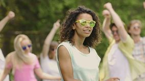 Young attractive woman dancing with group of friends at music festival, partying