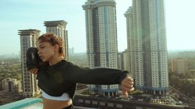 A young attractive woman is dancing and stretching with a cityscape against the backdrop of the rising sun. Freedom of stock footage