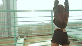 A young attractive woman is dancing and stretching with a cityscape against the backdrop of the rising sun. Freedom of. Choice, self-expression, not to be like stock video footage