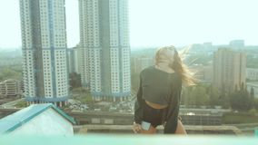 A young attractive woman is dancing and stretching with a cityscape against the backdrop of the rising sun. Freedom of. Choice, self-expression, not to be like stock footage