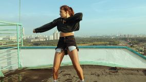 A young attractive woman is dancing and stretching with a cityscape against the backdrop of the rising sun. Freedom of stock video