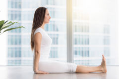 Young attractive woman in Dandasana pose against floor window Stock Photography