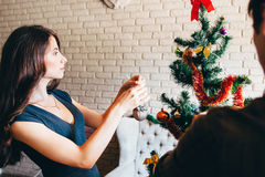 Young attractive woman decorating Christmas tree Stock Photos