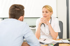 Young attractive woman doctor listening his patient Stock Photography