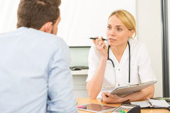 Young attractive woman doctor taking notes while patient speak Stock Images