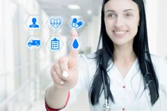Young attractive woman doctor touching icon of media screen. royalty free stock image