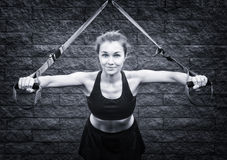 Young attractive woman does suspension training Royalty Free Stock Images