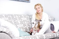 Young attractive woman with dog at home. Portrait of young attractive woman with dog at home Stock Image