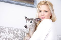 Young attractive woman with dog at home. Portrait of young attractive woman with dog at home Royalty Free Stock Photos