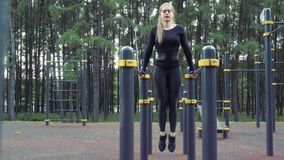 Young attractive woman doing abdominal muscle exercises outdoors.  stock footage