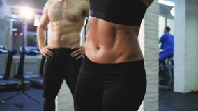 Young attractive woman doing basic abs oblique workout with fitness belts in gym studio, a man of athleticism watching stock video