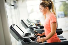 Young attractive woman doing cardio training in gym royalty free stock photography