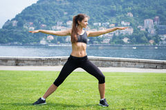 Young attractive woman doing exercises outdoors Stock Image