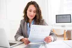 Young attractive woman doing paperwork. View of a Young attractive woman doing paperwork Stock Photography