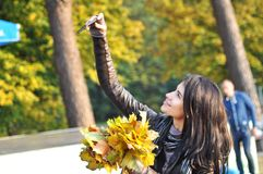 Young attractive woman doing selfie with a bouquet of autumn yellow leaves. Amazing season autumn is here Royalty Free Stock Photos