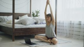 Young attractive woman doing yoga exercise and watching tutorial lesson on laptop computer at home Royalty Free Stock Images