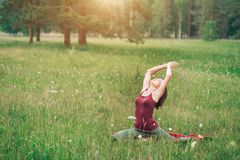 Young attractive woman doing yoga on the field royalty free stock photography