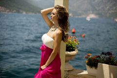 Young attractive woman in a dress relaxing by the sea. At sunny day Stock Image