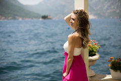 Young attractive woman in a dress relaxing by the sea. At sunny day Royalty Free Stock Photo