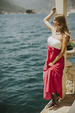 Young attractive woman in a dress relaxing by the sea. At sunny day Stock Photo
