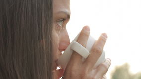 Young attractive woman drinking coffee or tea on the balcony, close-up stock footage