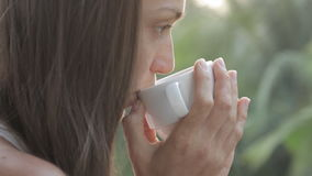 Young attractive woman drinking coffee or tea on the balcony, close-up stock video footage