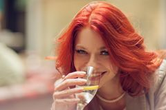 Young attractive woman drinking a glass of water in a street cafe stock photography