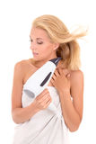 Young attractive woman drying her hair with hairdryer Stock Photo