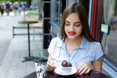 Young attractive woman eating cake with coffee in outdoor cafe Royalty Free Stock Images