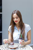 Young attractive woman eating cake with coffee in outdoor cafe. Young attractive woman with long hair  eating cake with coffee in outdoor cafe Royalty Free Stock Image
