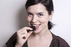 Young attractive woman eating chocolate Stock Photography