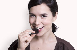 Young attractive woman eating chocolate Stock Images