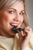 Young attractive woman eating grape. In studio Stock Photos