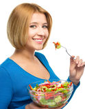 Young attractive woman is eating salad using fork Stock Image