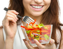 Young attractive woman is eating salad using fork Royalty Free Stock Image