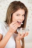 Young attractive woman eating yogurt Stock Photo