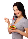 Young attractive woman eats vegetable salad Royalty Free Stock Photography