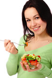 Young attractive woman eats vegetable salad Royalty Free Stock Photos