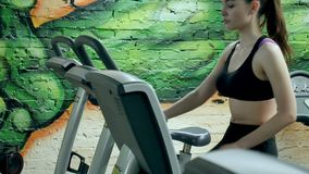 Young attractive woman enhancing her endurance while working out on an exercycle. portrait of a beautiful girl in the stock video footage