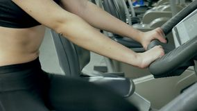 Young attractive woman enhancing her endurance while working out on an exercycle. portrait of a beautiful girl in the. Gym on a stationary bike. young woman on stock footage