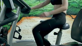 Young attractive woman enhancing her endurance while working out on an exercycle. portrait of a beautiful girl in the. Gym on a stationary bike. young woman on stock video